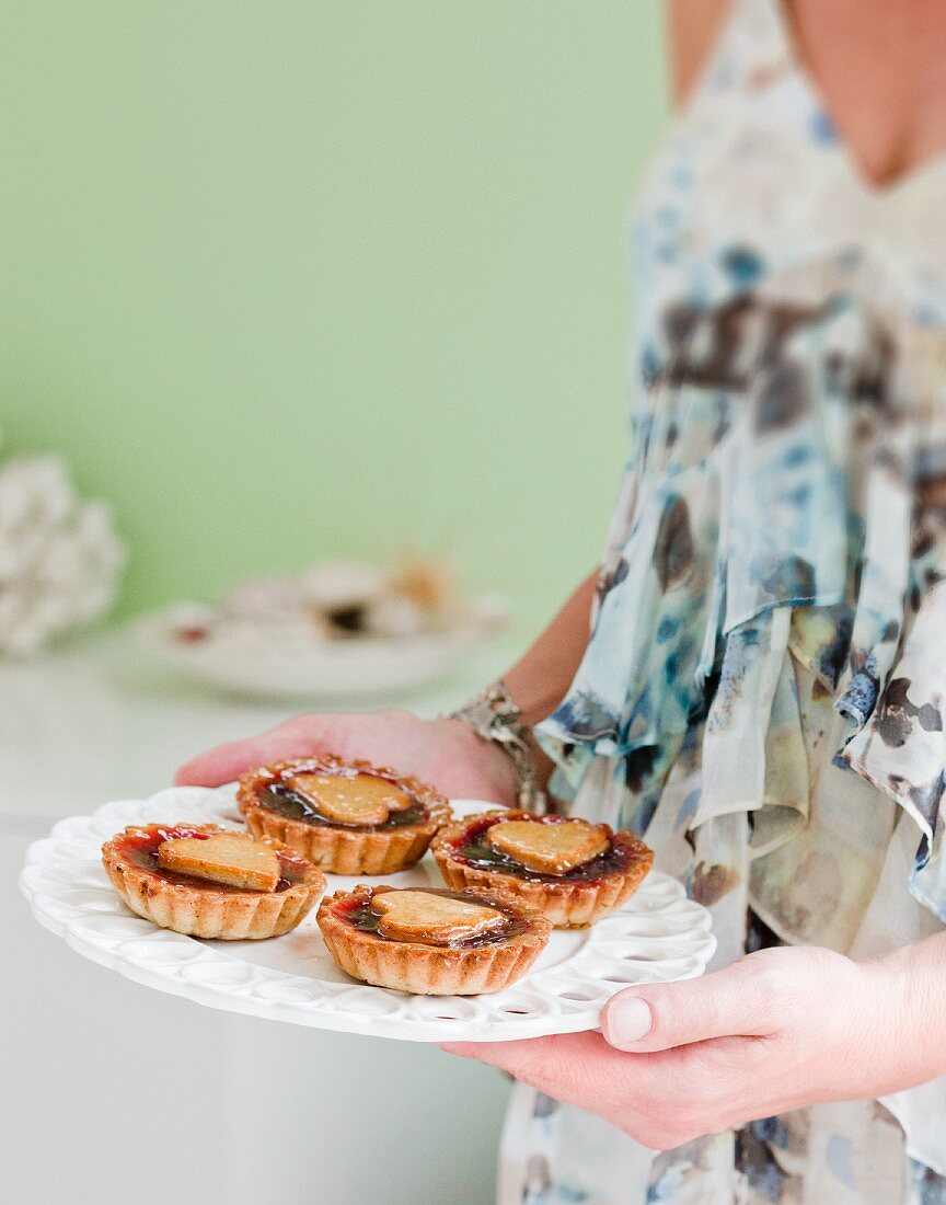 A woman serving jam tartlets with heart-shaped lids
