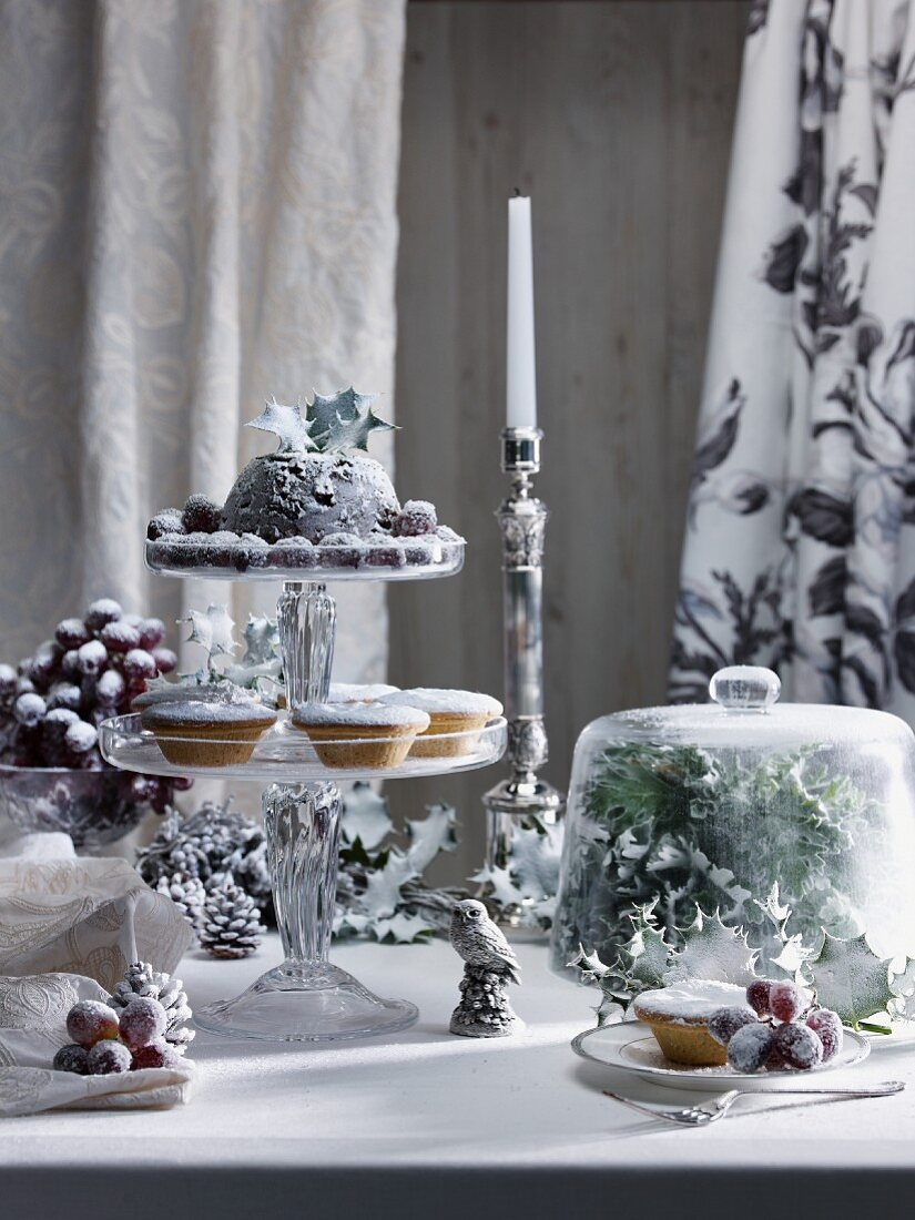 A Christmas table with mince pies, Christmas pudding and sugared grapes