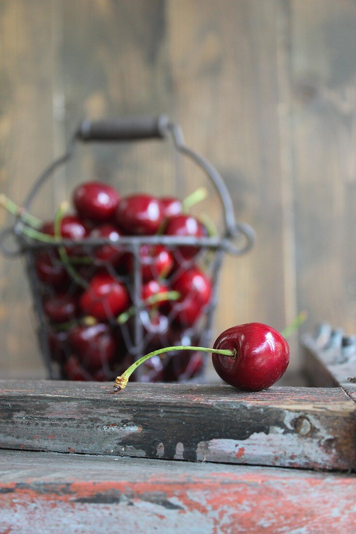 Fresh cherries in a wire basket and in front of it