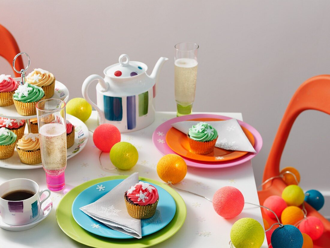 A brightly coloured table laid for Christmas with a string of lights and snowflake decorations on coloured plates and cupcakes