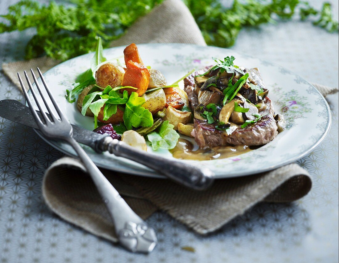 Beef steak with a mushroom sauce and root vegetables