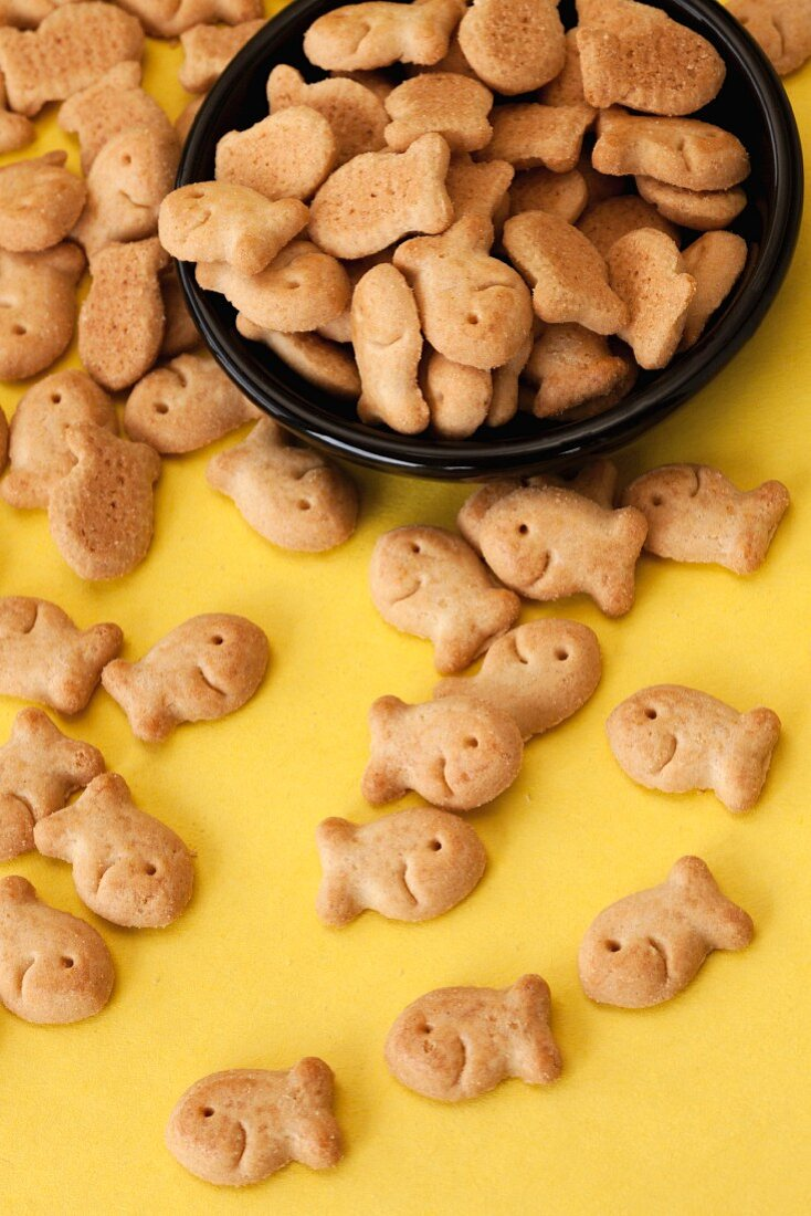 Goldfish crackers in a black bowl on a yellow surface