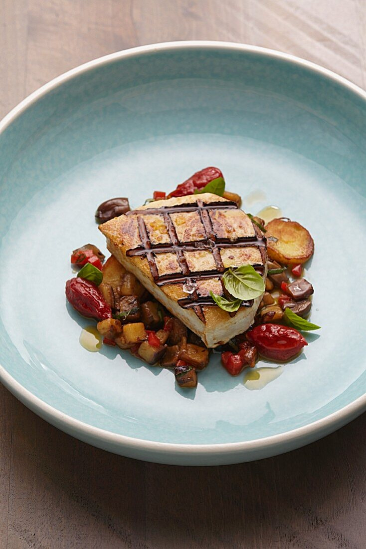Grilled swordfish steak with aubergines and oven-roasted tomatoes