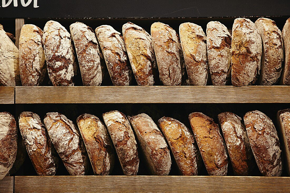 Loaves of organic bread on a wooden shelf in a bakery