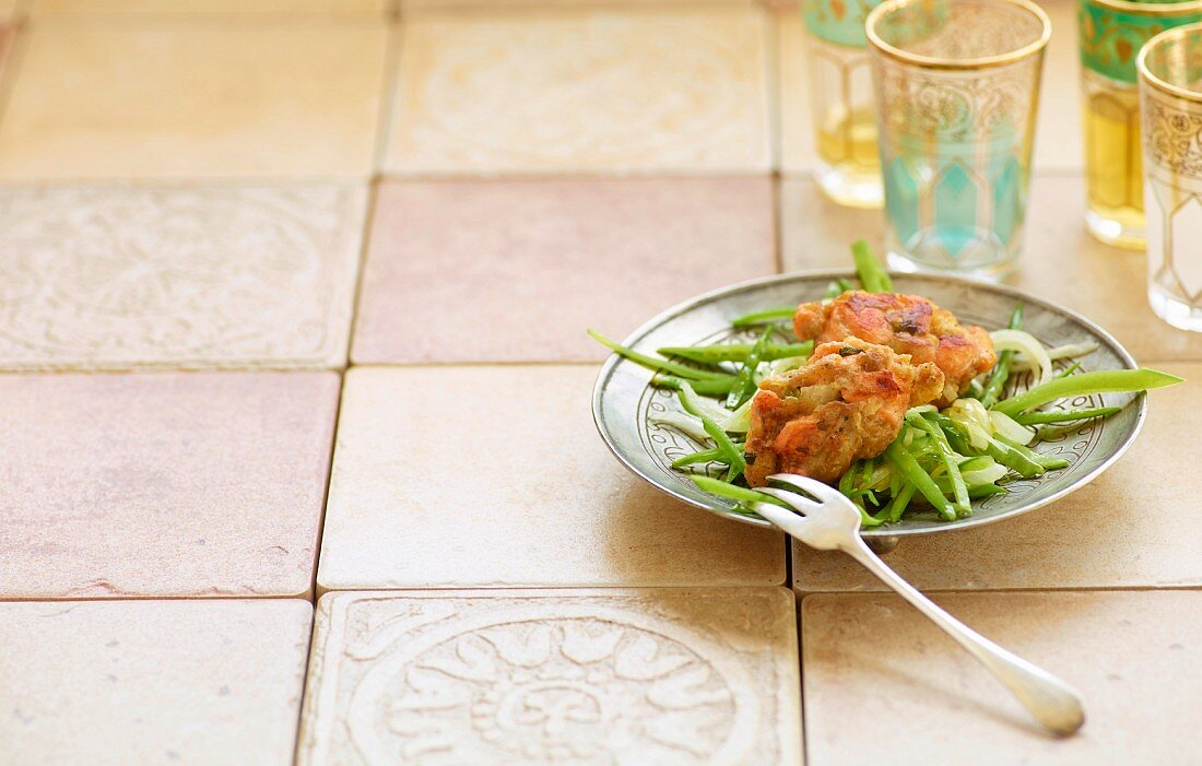 Mini salmon cakes on a bed of mange tout