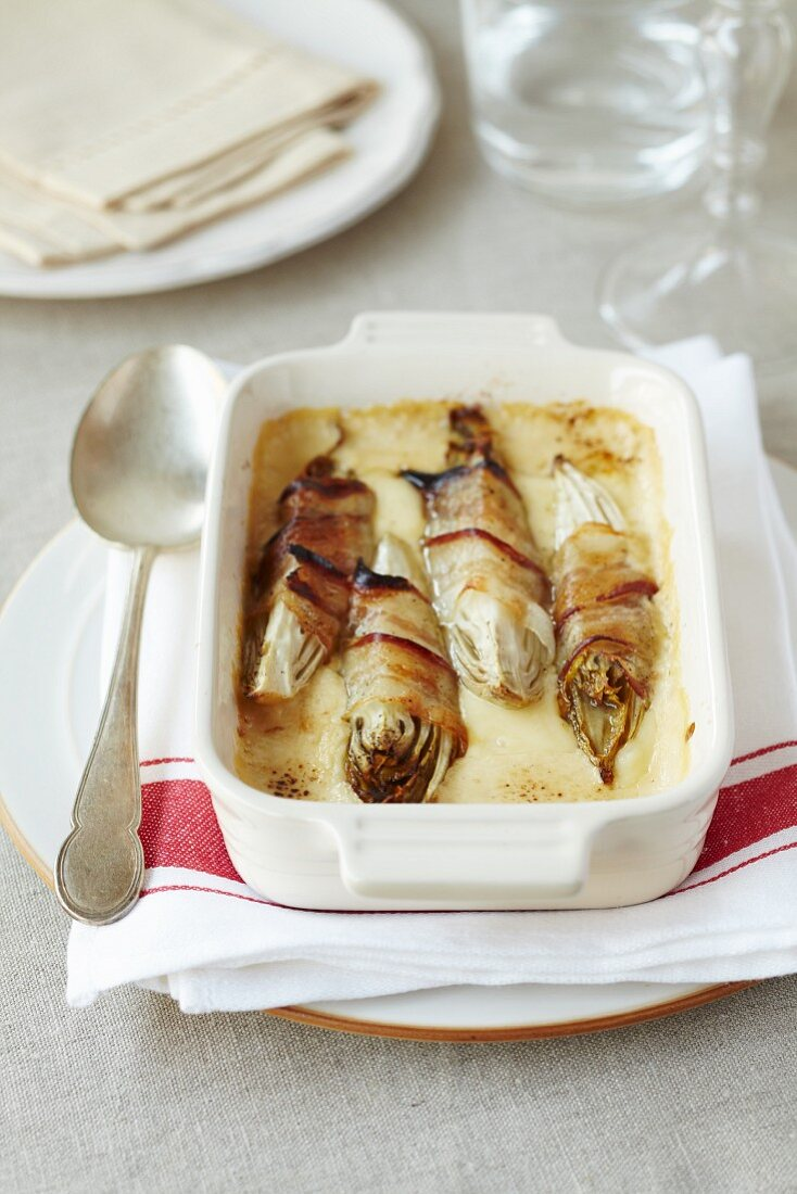 Gratinated radicchio wrapped in bacon with cheese sauce