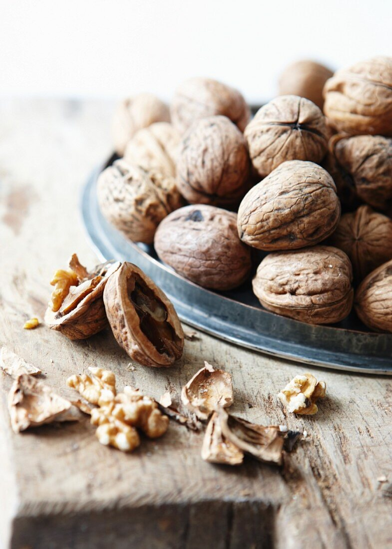 Walnuts on a metal lid on a rustic table