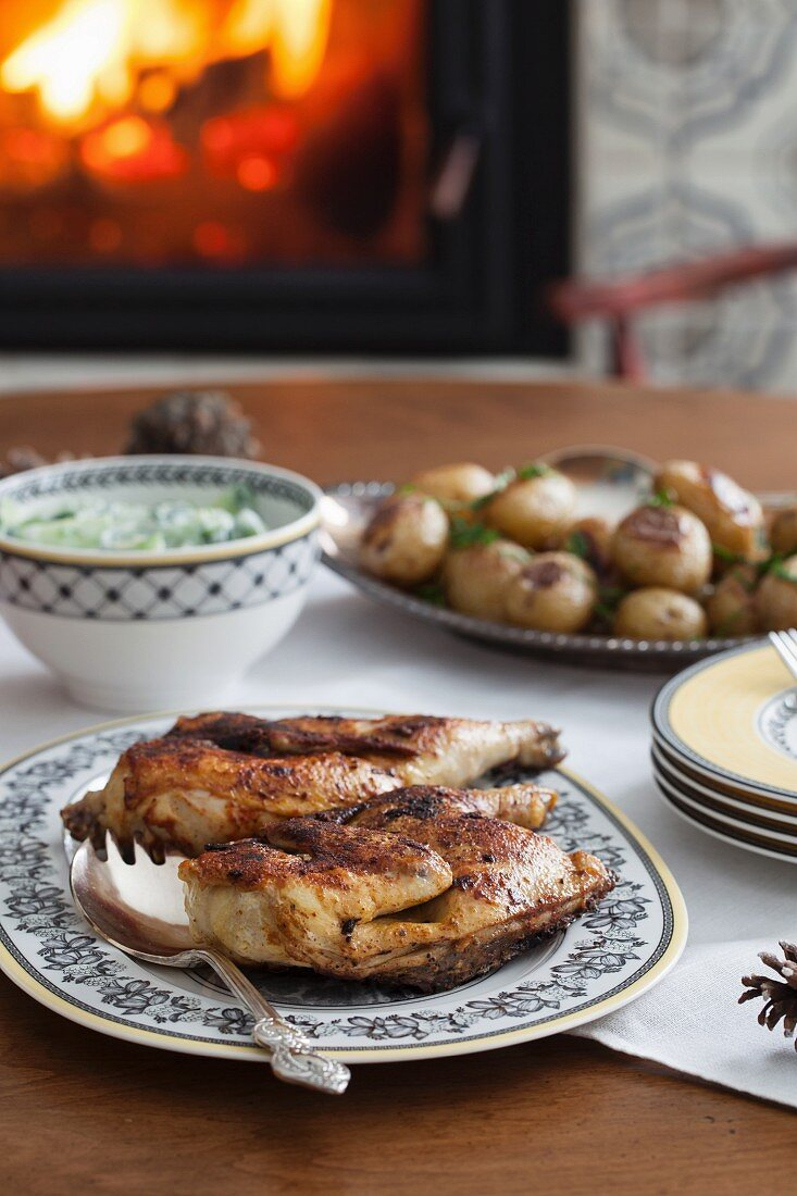 Chicken with potatoes for dinner in front of a fire