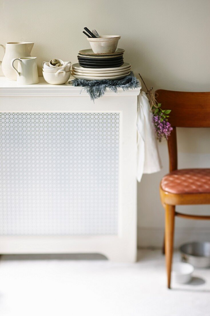 A stack of crockery and jugs on a kitchen sideboard
