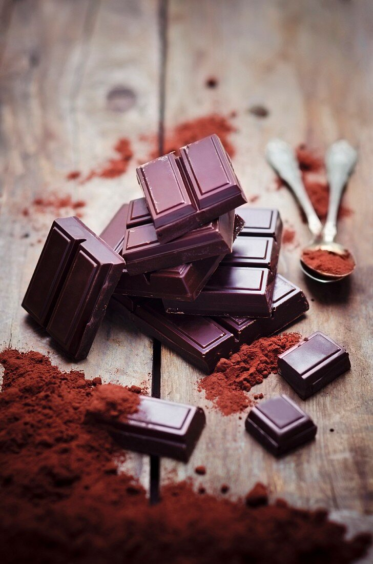 Bitterschokolade, Teelöffel und Kakaopulver auf Holzuntergrund