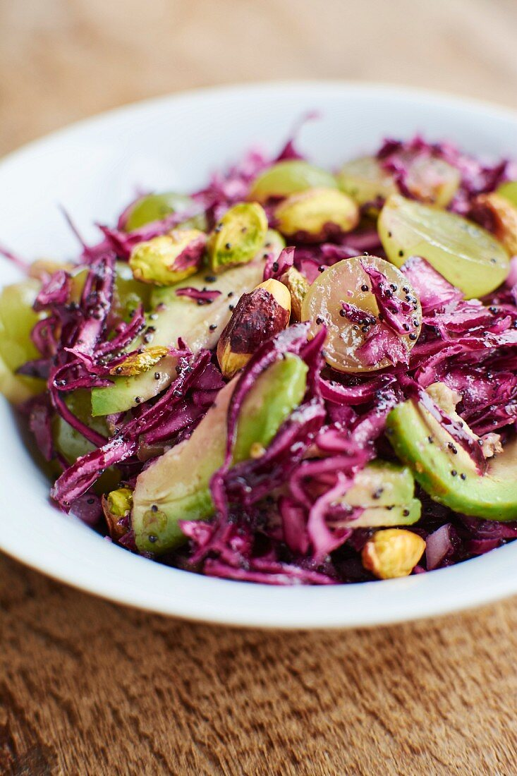 Red cabbage salad with avocado, grapes, pistachios and poppy seed dressing