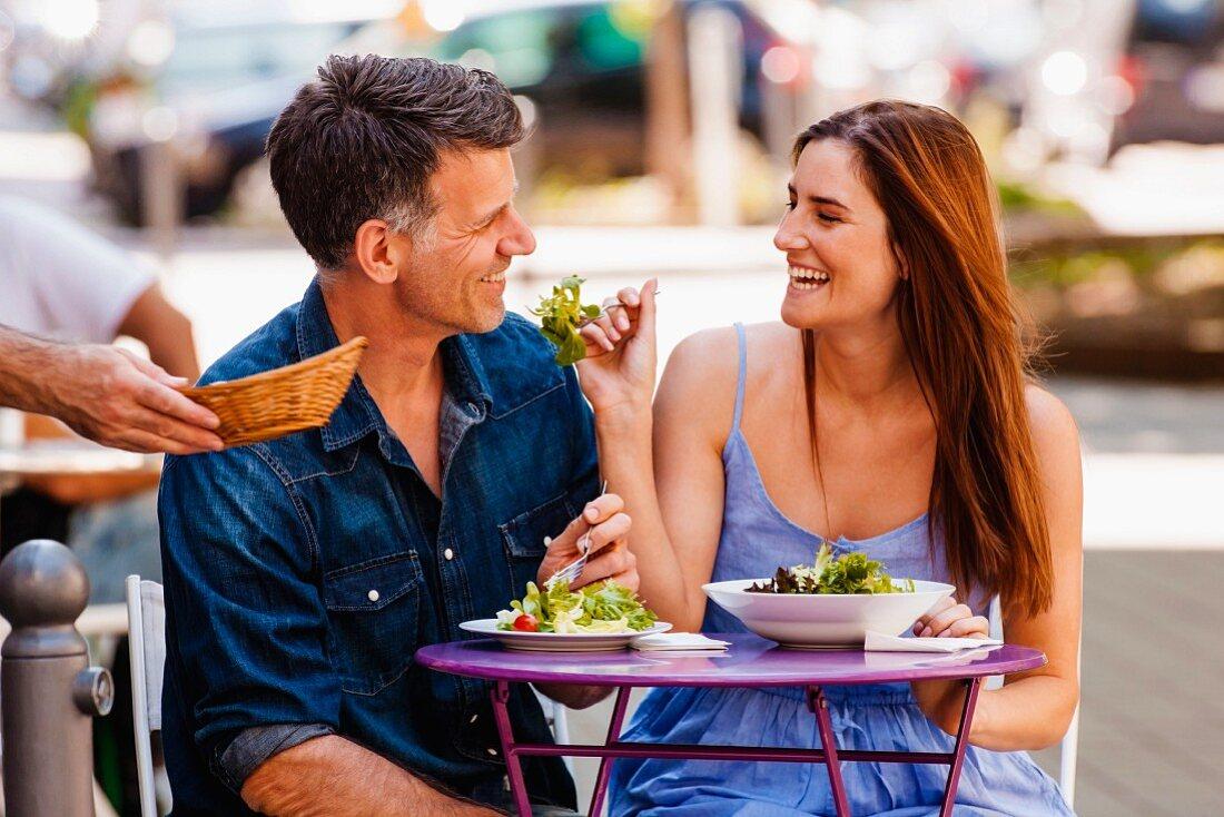 Couple enjoying food in pavement restaurant