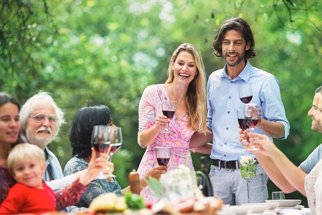 A couple raising glasses of red wine at a garden party