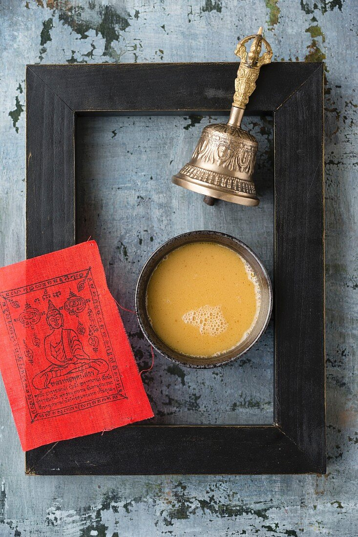 A bowl of butter tea, a red prayer flag and a bell inside a black picture frame (Tibet)