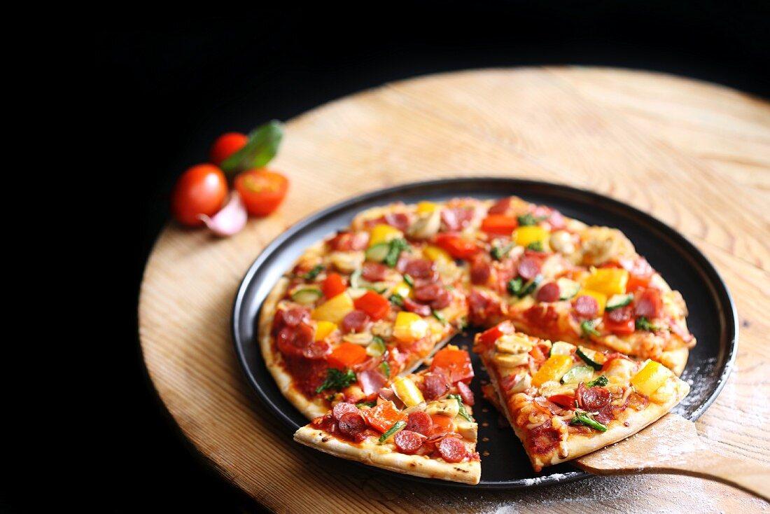 Pizza mit Gemüse und Wurst, angeschnitten