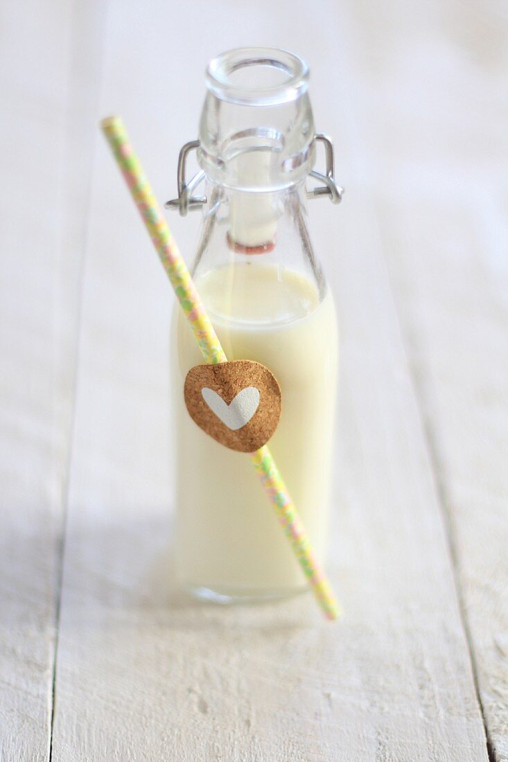 A bottle of milk with a straw and a heart decoration