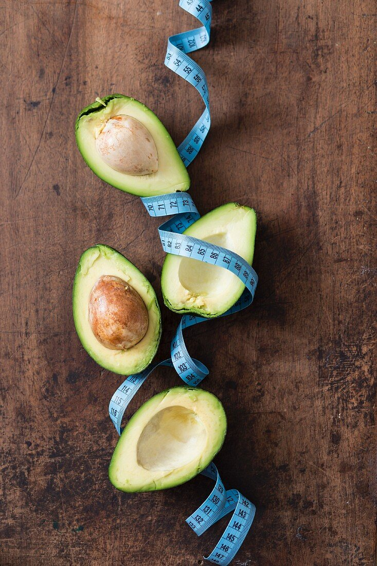 Avocado halves and a measuring tape on a wooden surface