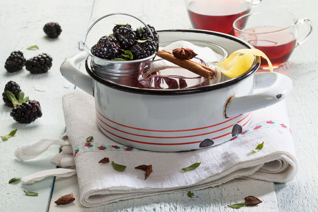 Glass cups of mulled wine, ingredients and cooking utensils