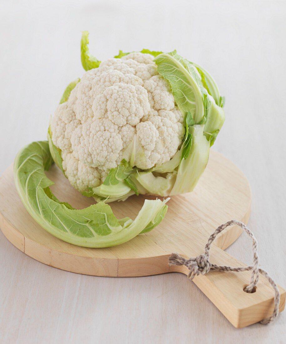 A cauliflower on a light wooden chopping board