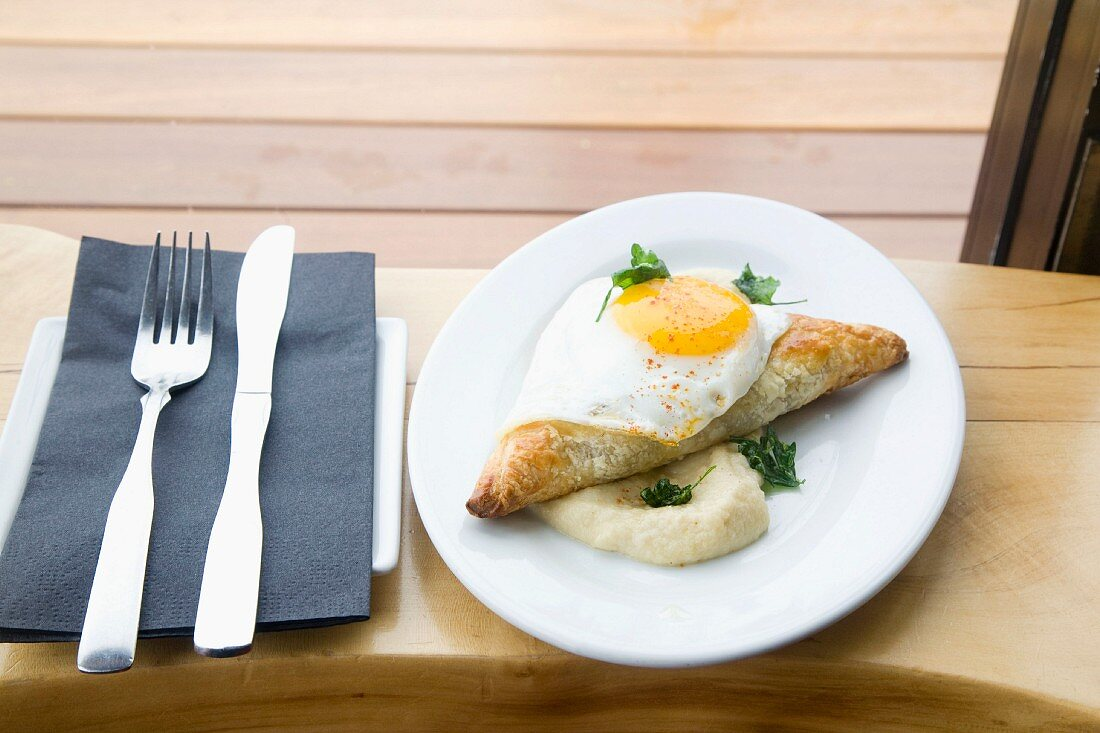 A spicy filled puff pastry with a fried egg