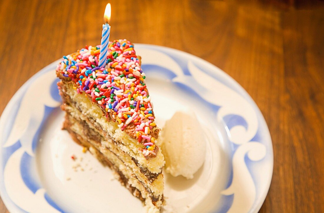 A colourful slice of birthday cake with a burning candle and a scoop of vanilla ice cream