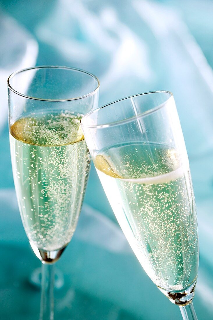 Two champagne glasses clinking together