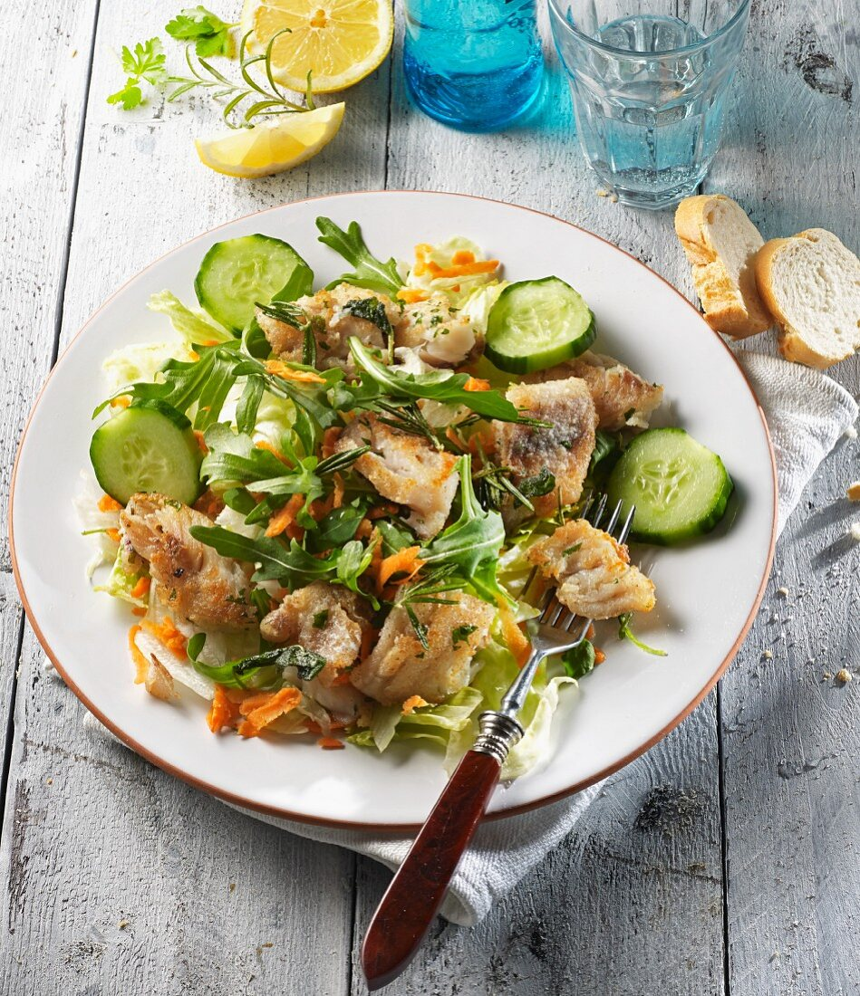 A mixed salad with fried red snapper and herbs