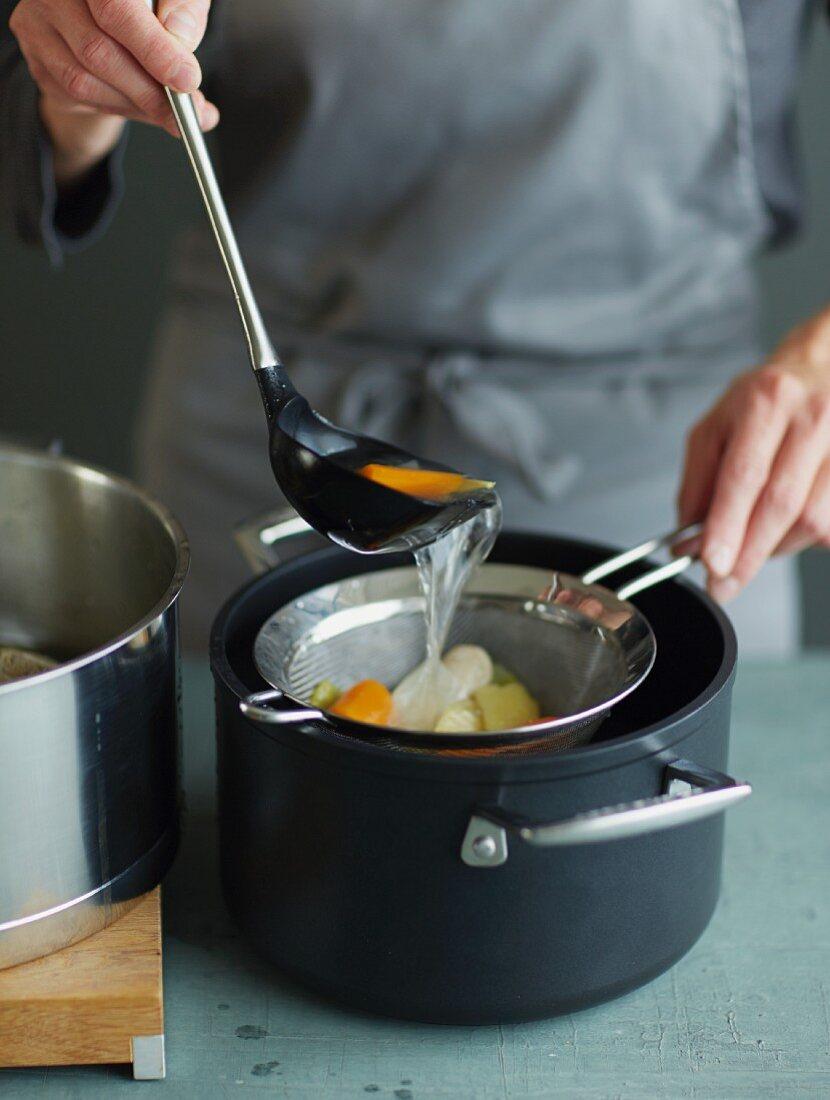 Tom Ka Gai (Thai chicken soup) being made: broth being sieved