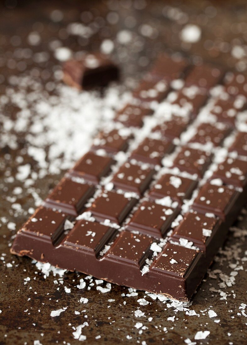 A bar of dark chocolate sprinkled with sea salt flakes