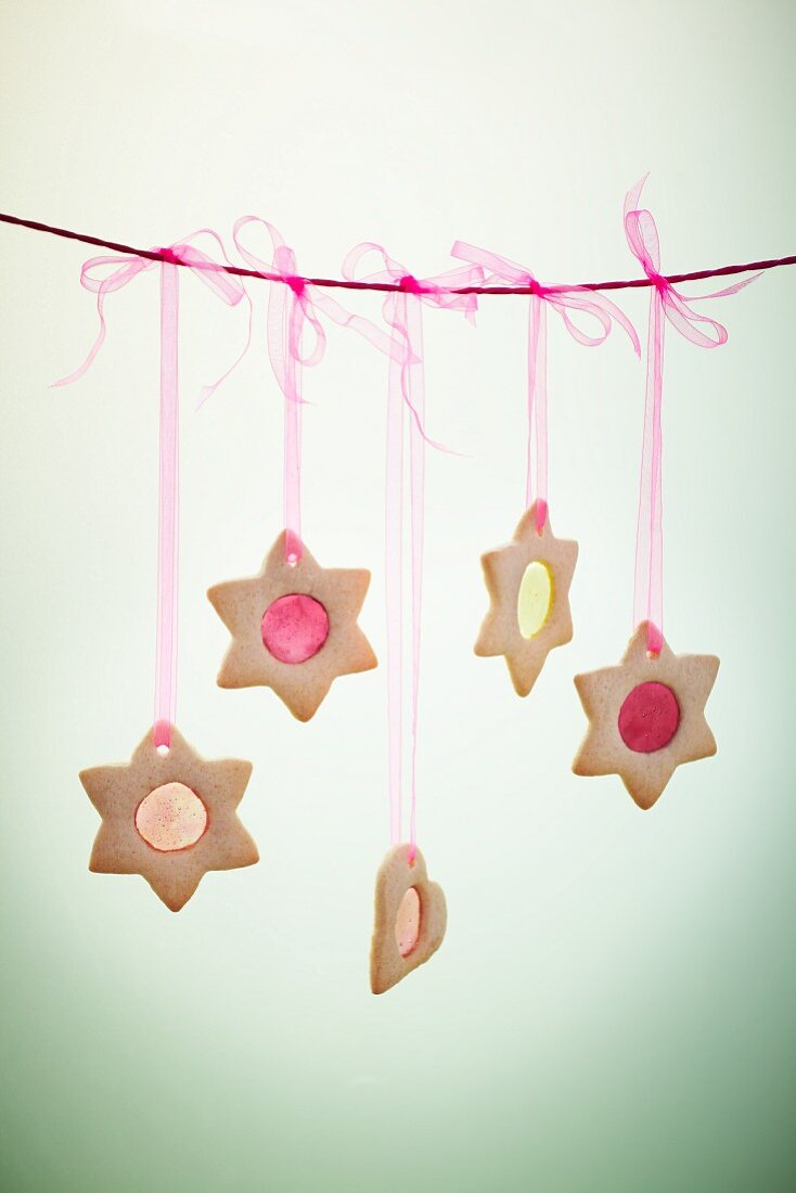 Star and heart-shaped biscuits with translucent sugar windows hung on a line