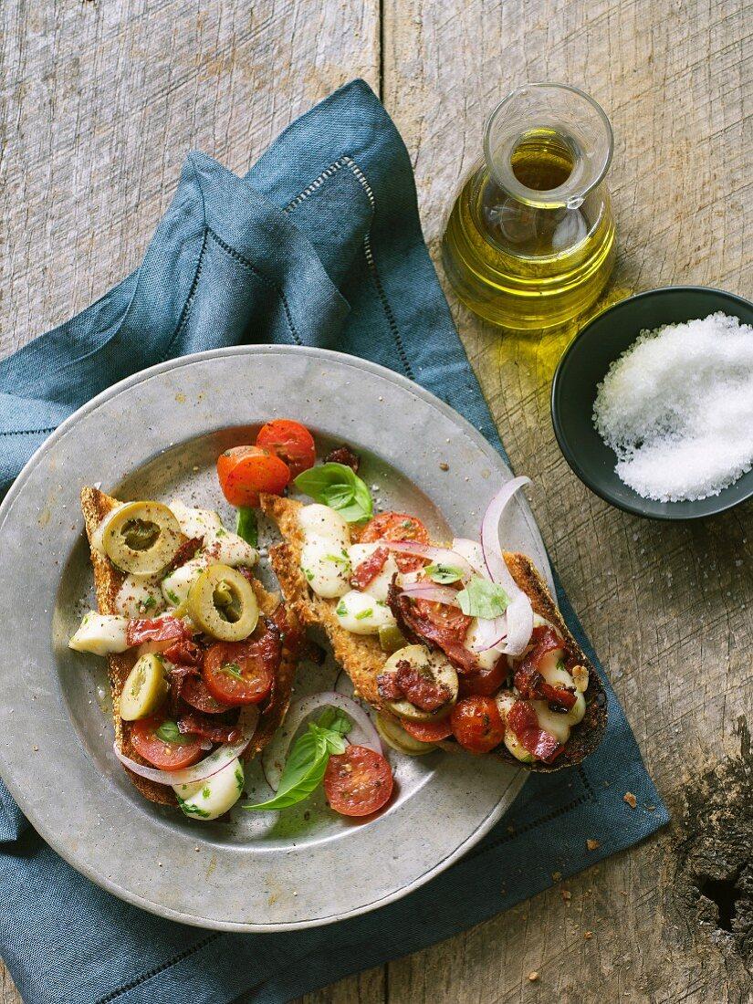 Bruschetta with caprese, prosciutto and olives