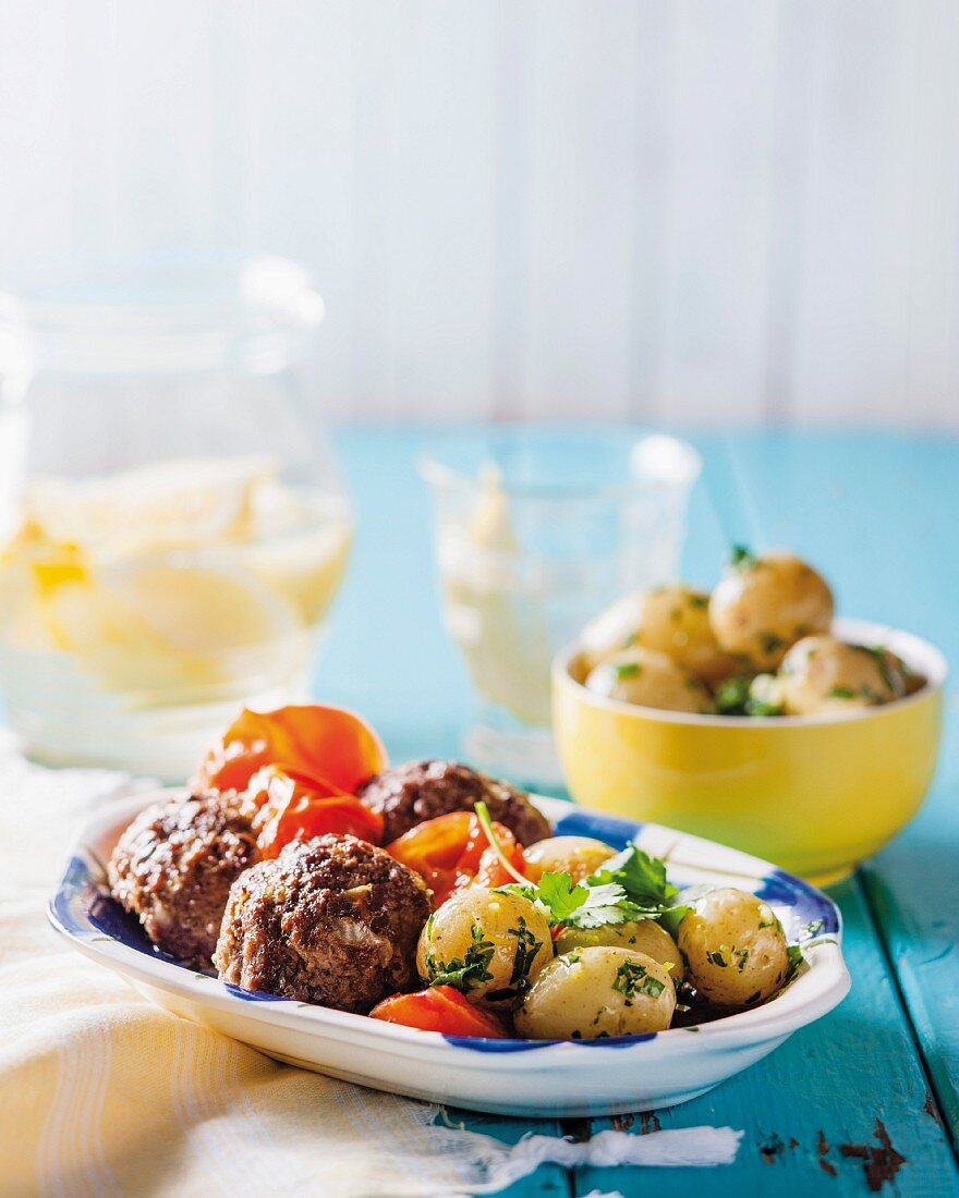 Oven-baked meatballs with tomatoes and gremolata potatoes