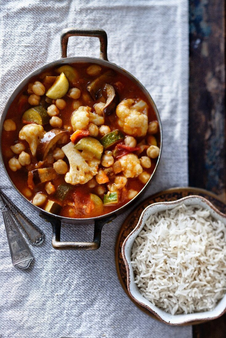 Vegetable curry with chickpeas, aubergines, courgettes, cauliflower and tomato in a pot served with a bowl of jasmine rice