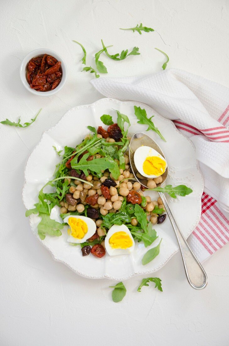 Chickpea salad with dried tomatoes, rocket, olives and hard-boiled egg