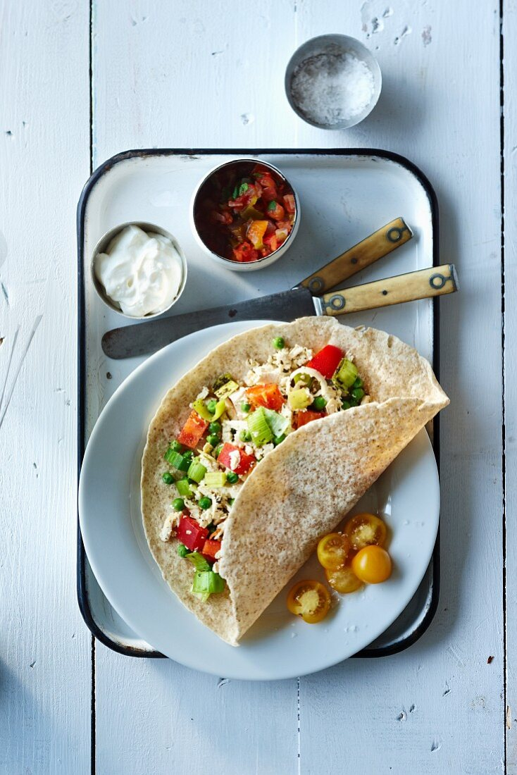 Burrito with fish, leek, pepper, peas and tomato served with tomato salsa and sour cream