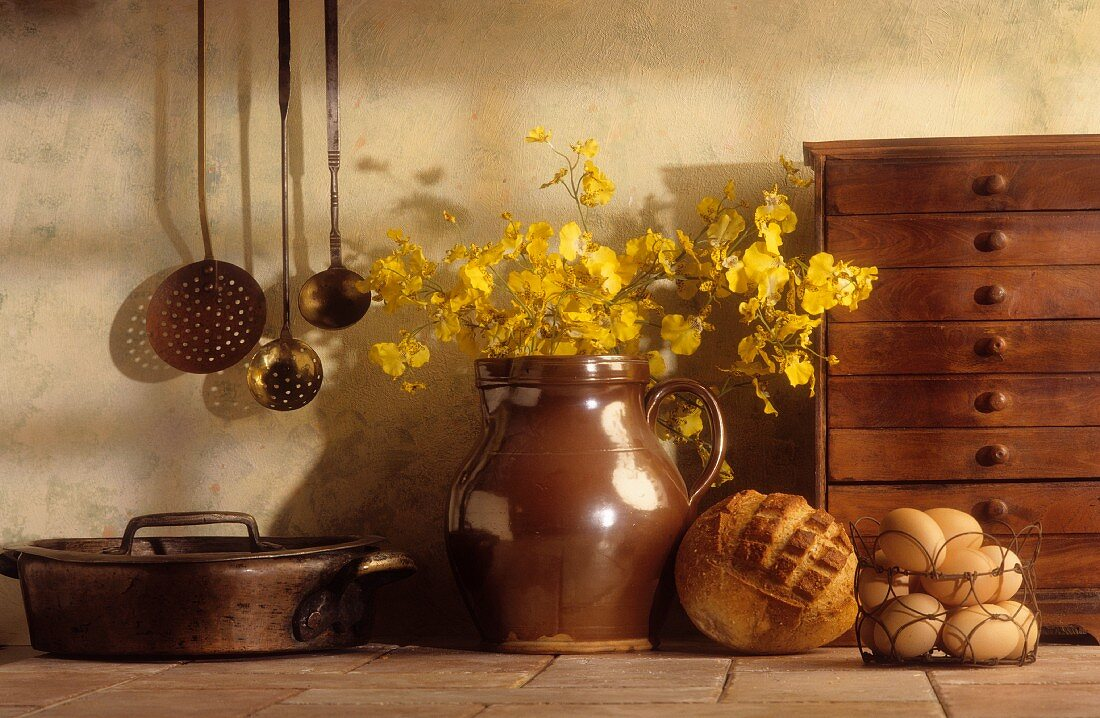 An arrangement of kitchen utensils, a chest of drawers, an earthenware jug, bread and eggs