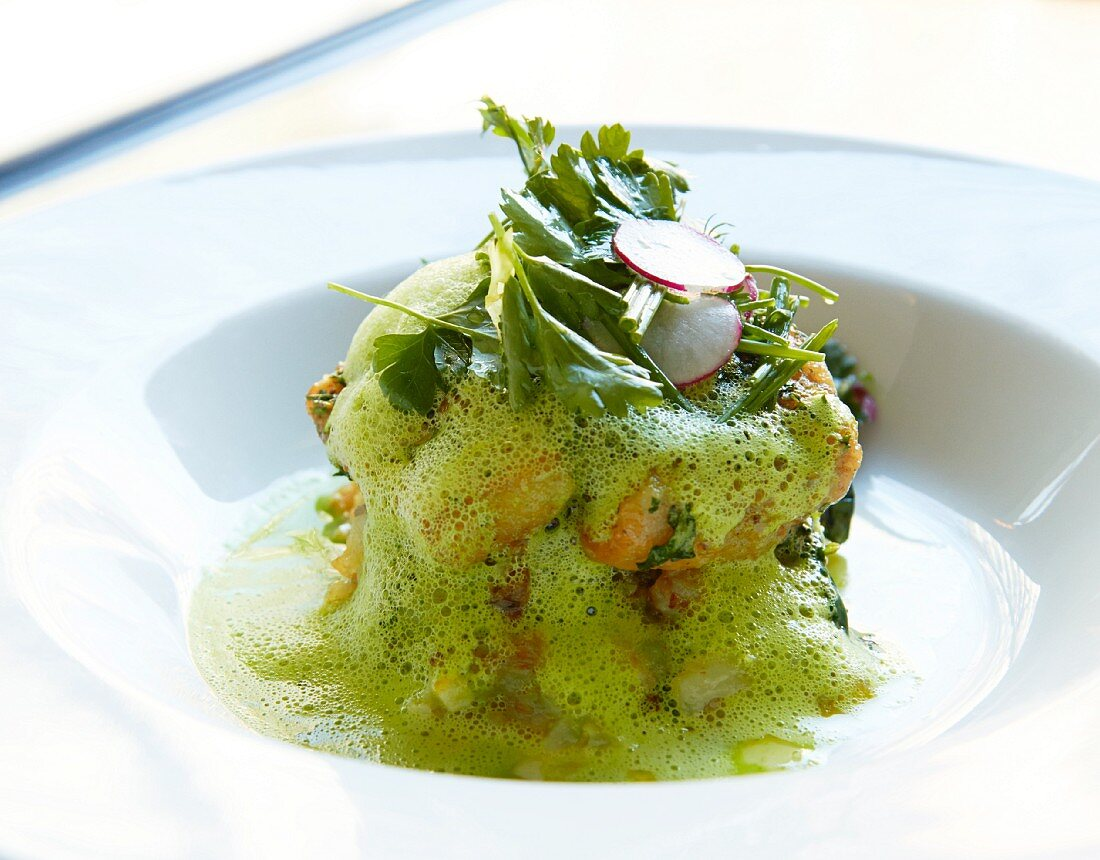 A stack of fried potatoes with a foamy spinach sauce, gremolata and herbs