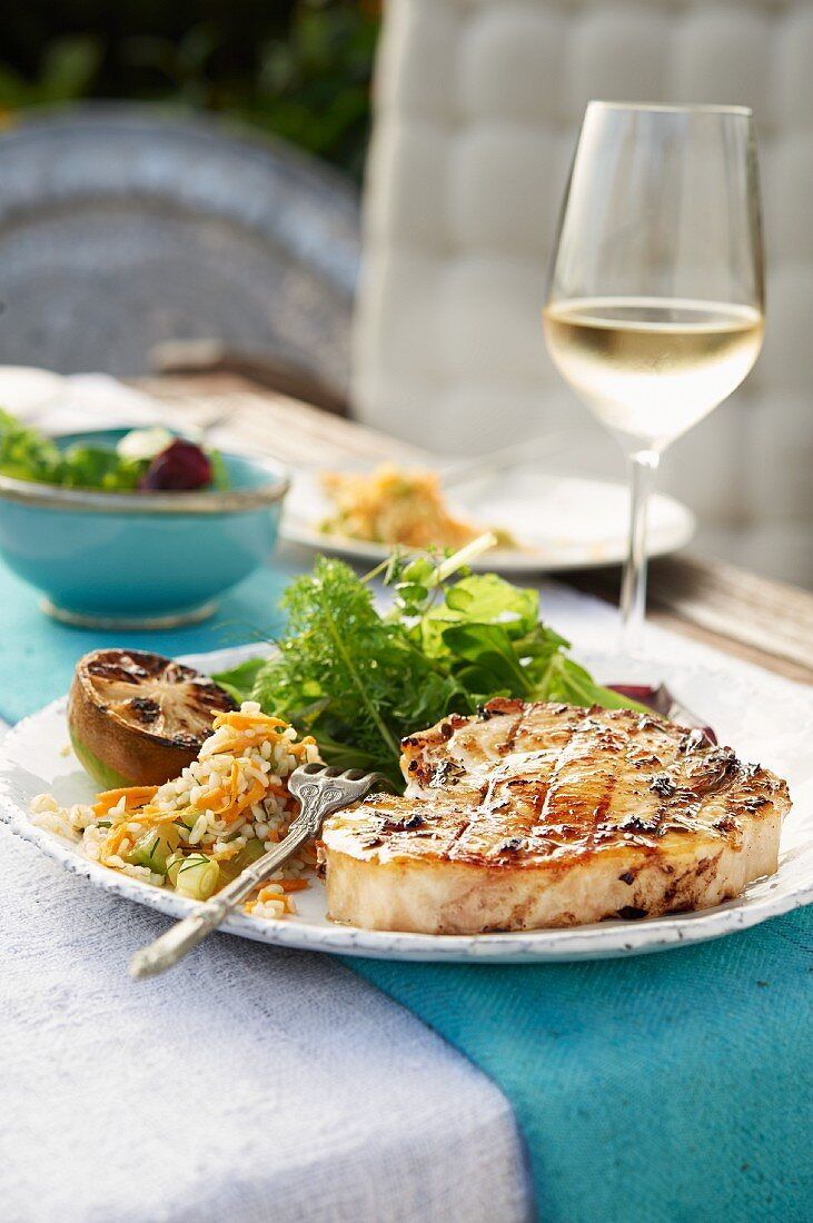 Grilled swordfish steak with lettuce and lime