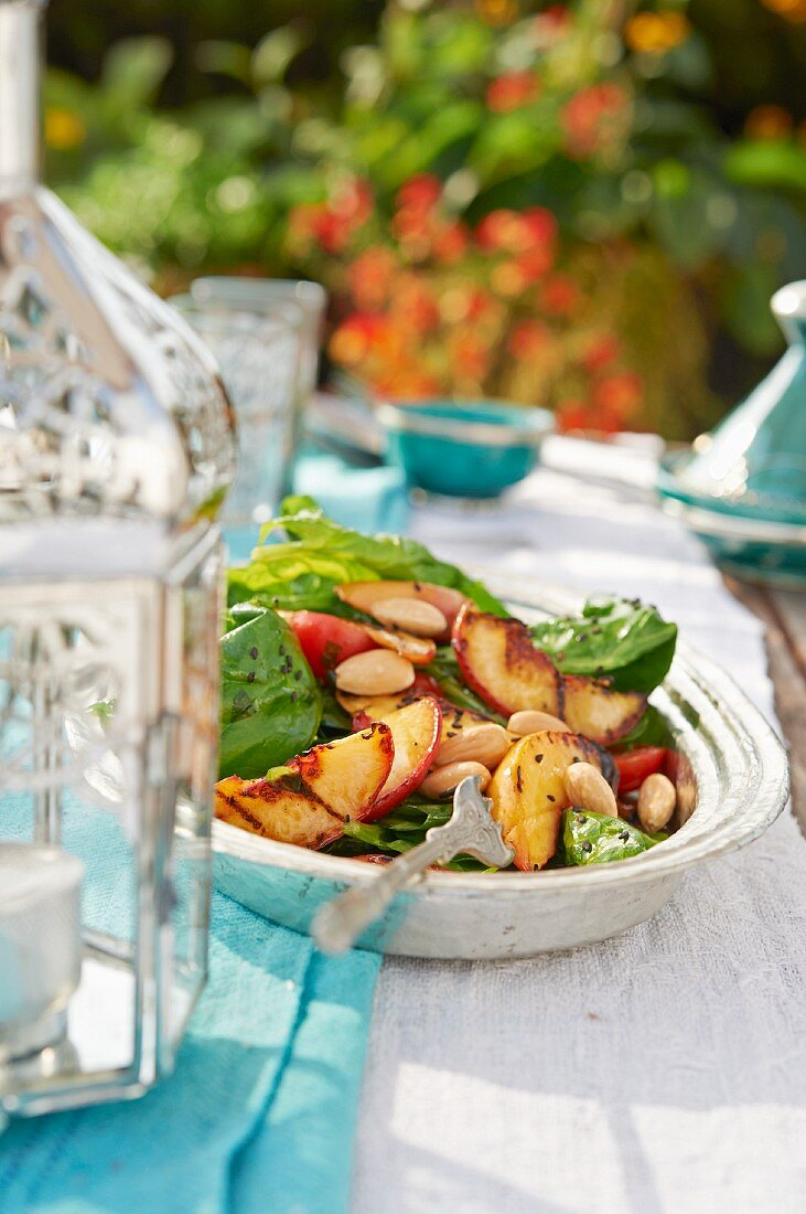 Spinach and tomato salad with almonds and peaches