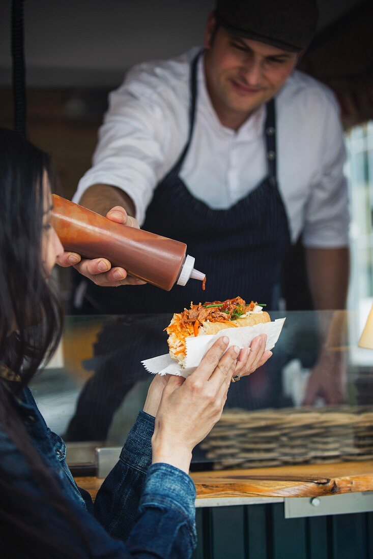 A seller pouring barbecue sauce onto a customer's sandwich