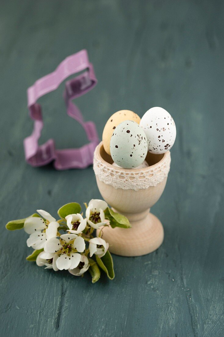 Sugar-coated chocolate eggs in wooden egg cup and pear blossom