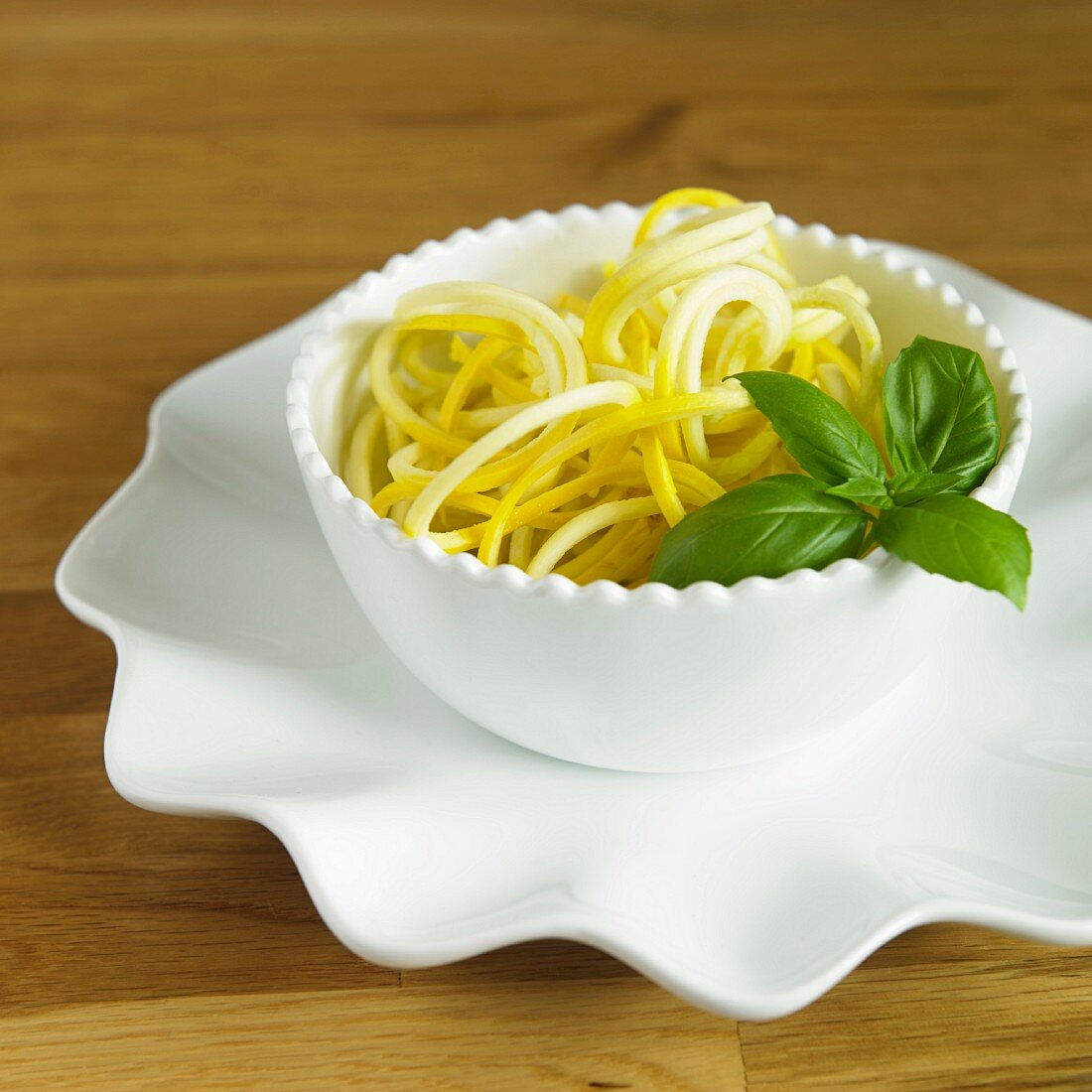 Yellow courgette spaghetti with basil in a white bowl