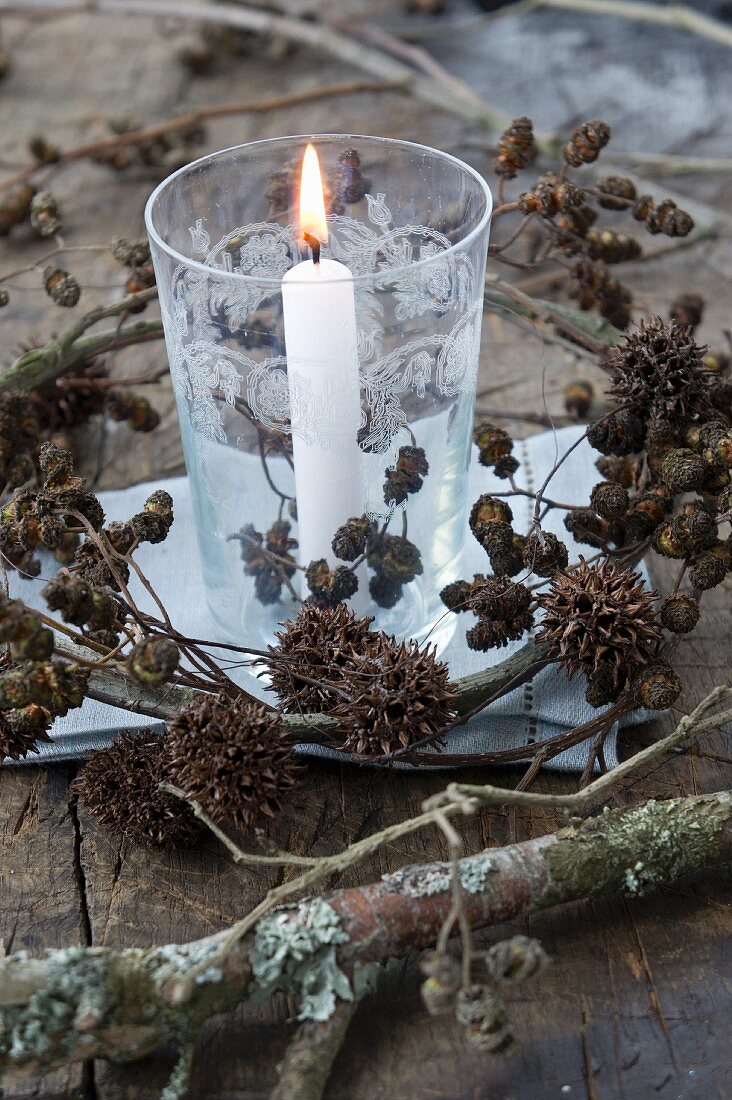 A lantern with a wreath of alderberry sprigs and maple fruit sprigs
