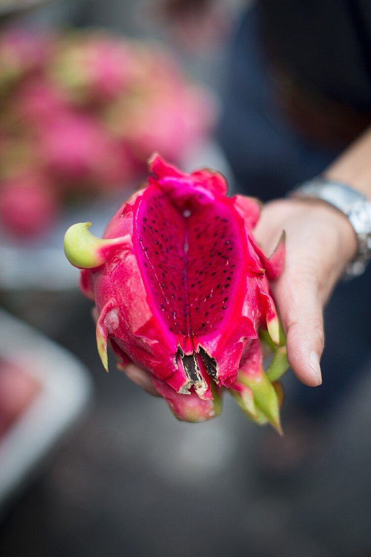 A hand holding a dragon fruit at a market in Saigon, Vietnam