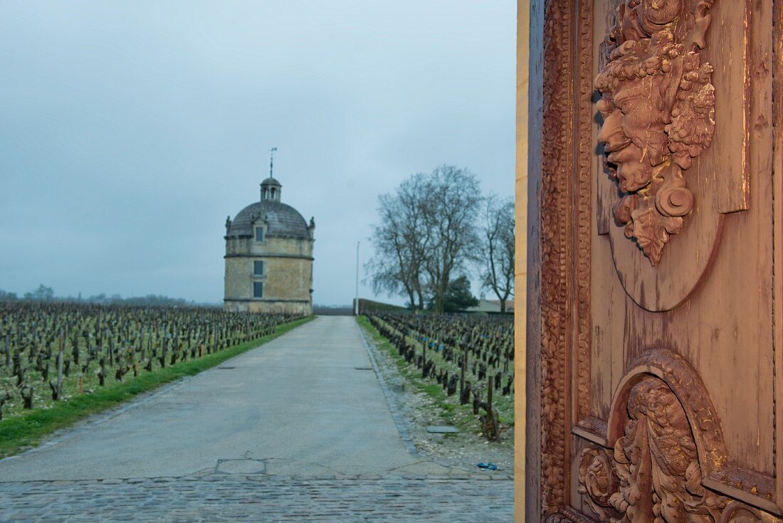 A view of a tower at the Chateau Latour vineyard through a wooden gate (Bordeaux, France)