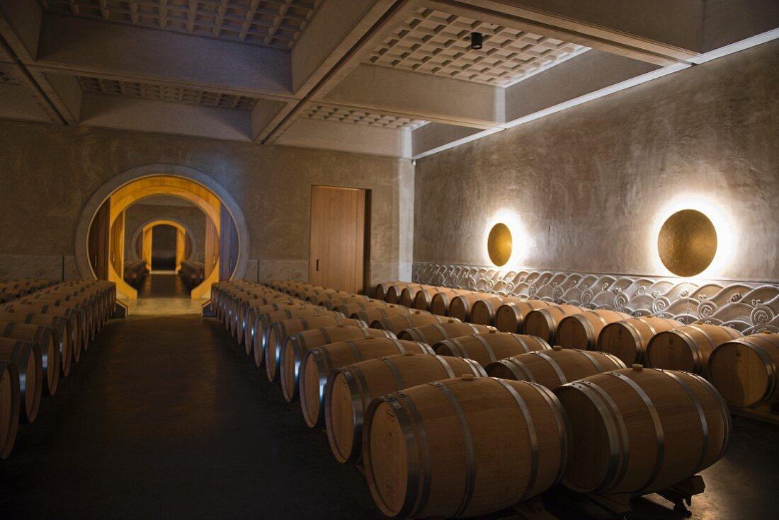 Barrique barrels in the wine cellar at Chateau Fourcas Hosten (Bordeaux, France)