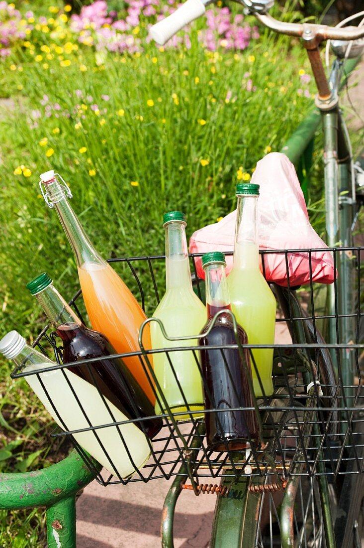 Bottles of various homemade lemonades in a bike basket