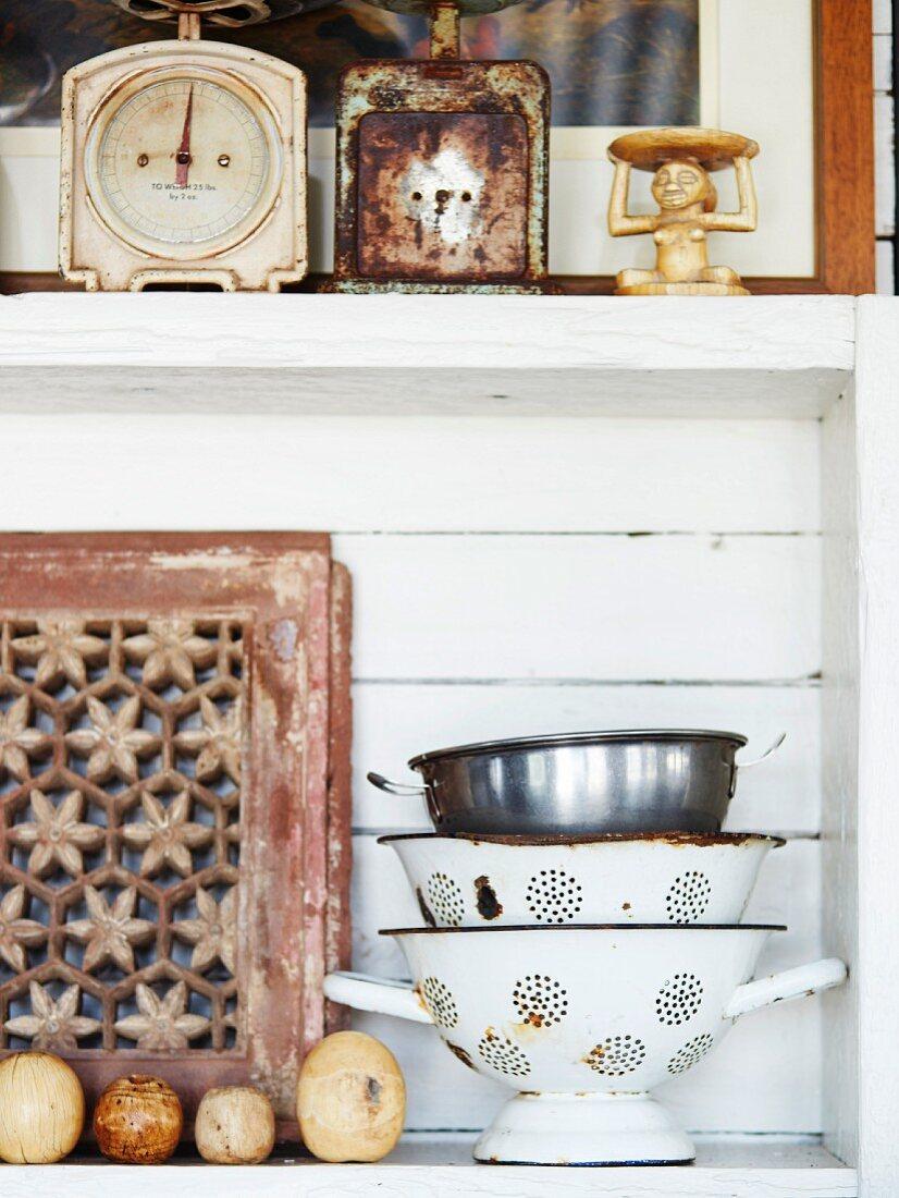 Vintage metal colanders and old kitchen scales on wooden kitchen shelves