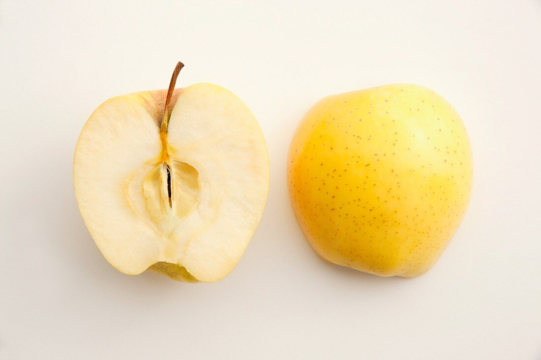 A halved Golden Delicious on a white surface