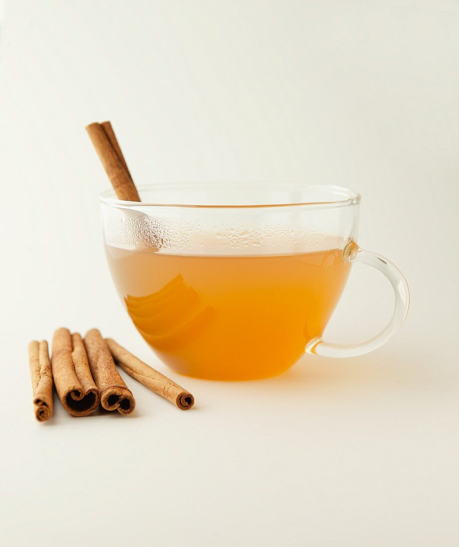 Hot cider with cinnamon in a glass cup on a white surface